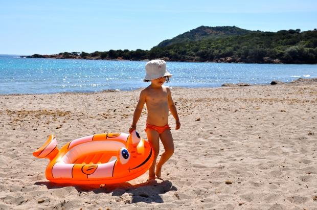 plage de rondinara, enfant avec un bob et une bouée orange en forme de poisson clown