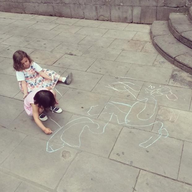 des enfants dessinent à la craie au sol