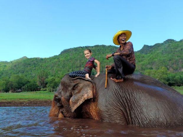 fillette à dos d'éléphant dans l'eau, Thaïlande