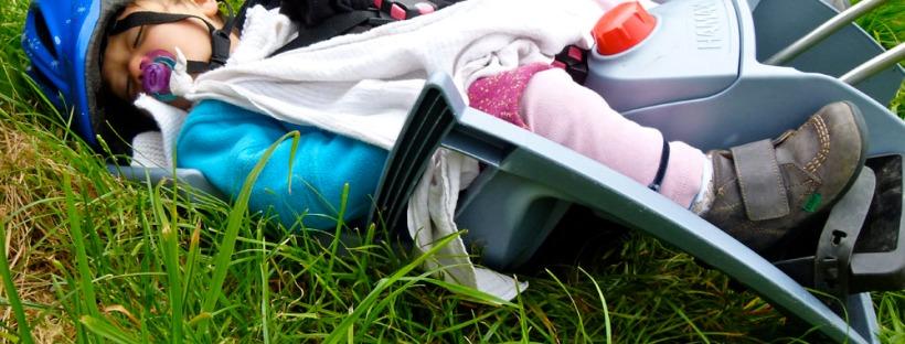 bébé dormant dans l'herbe dans son siege bébé à vélo avec son casque et sa sucette