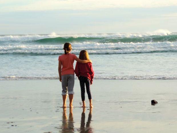 2 fillettes face aux vagues de la Plage des Moeraki Boulders, Asutralie