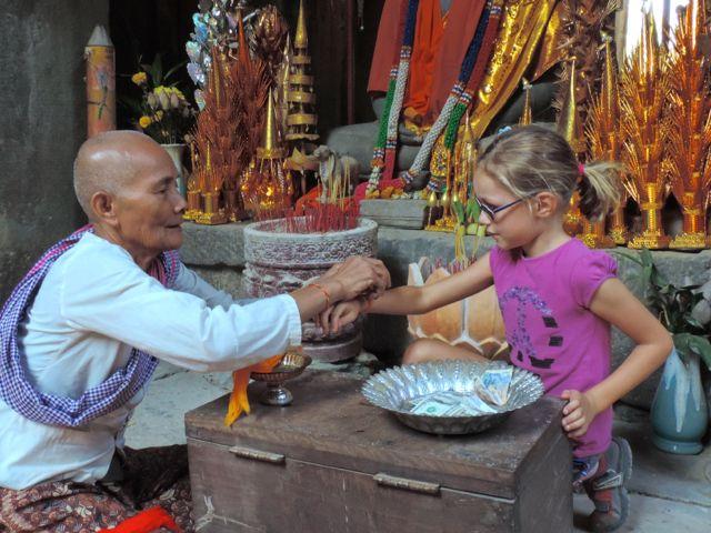 moine nouant bracelet au poignet d'une fillette, Ta Phrom, Cambodge