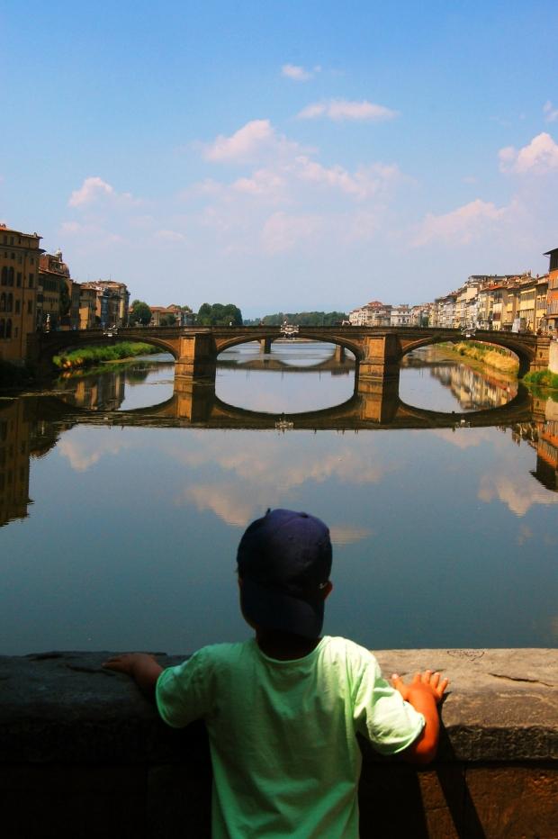 florence enfant de dos sur un pont à florence au dessus rivière toscane