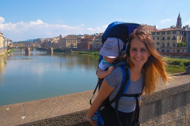 toscane femme avec enfant en porte-bébé sur un ont devant rivière