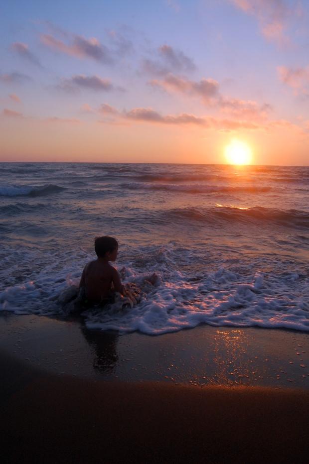 plage toscane coucher de soleil avec enfant les pieds dans l'eau