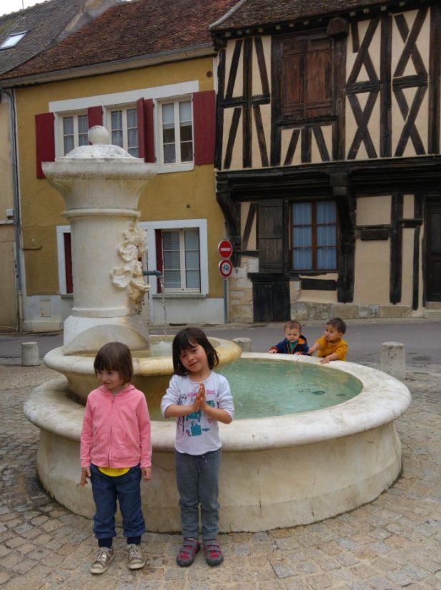 fontaine cravant avec enfants devant et maison à colombage