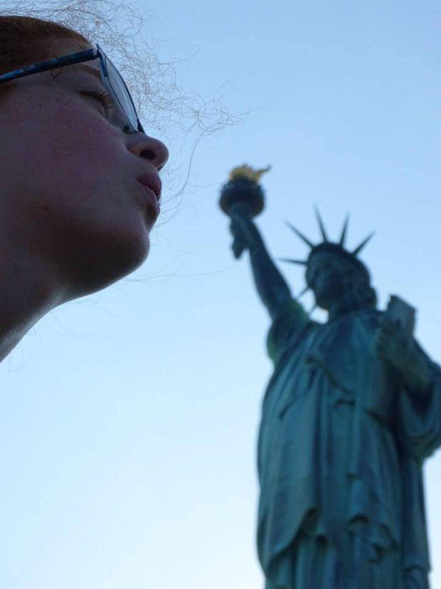 petite fille souffle sur la flamme de la statue de la liberté, NYC